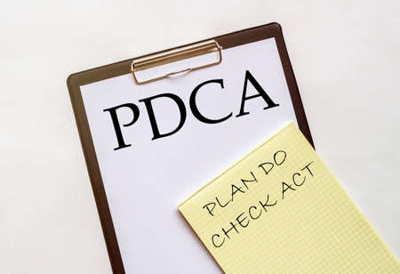 white and yellow paper with text PDCA Plan Do Check Act on a white background with stationery