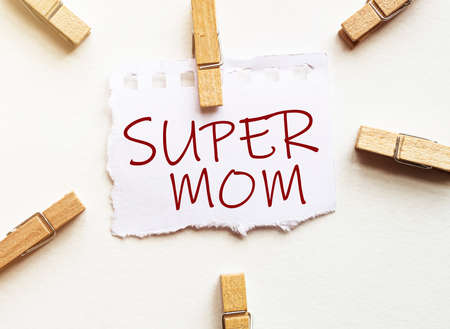 white paper with text Super Mom with clothespins on white background