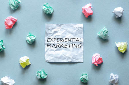 white paper with text Experiential Marketing on the blue background with a lot of another paper Standard-Bild