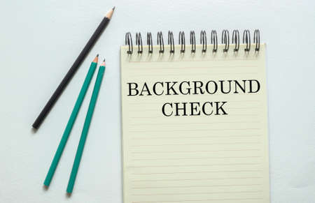 two green one black pencil with text Background Check in the notebook on the white background