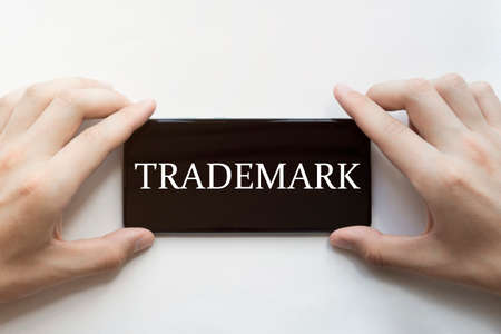 male hands are holding black phone with text Trademark on white background Stock Photo