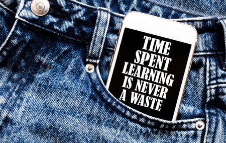 white phone with text Time Spent Learning Is Never A Waste lies in jeans pocket