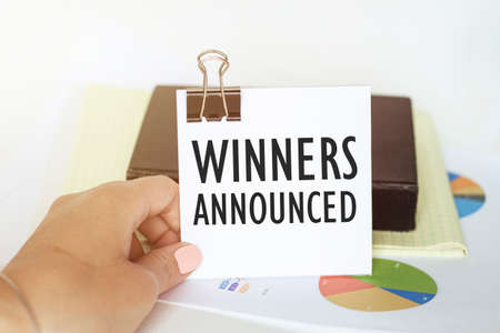 woman s hand holds a piece of paper with text Winners Announced on the background of graphs and notepad