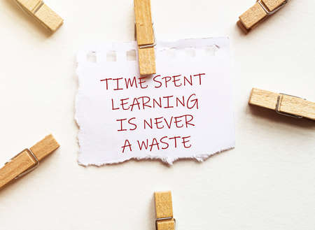 white paper with text Time Spent Learning Is Never A Waste with clothespins on white background