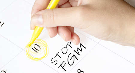 hand encircles a date on a calendar with text Stop Fgm yellow felt-tip pen
