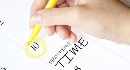 hand encircles a date on a calendar with text Shopping Time yellow felt-tip pen
