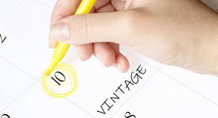 hand encircles a date on a calendar with text vintage yellow felt-tip pen