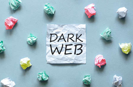 white paper with text Dark web on the blue background with a lot of another paper