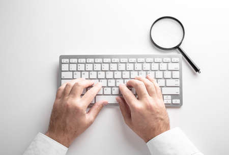 black magnifier on a white keyboard on a white background. Business concept.
