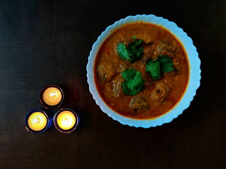 Malai Kofta, Mughlai Speciality dish made with Deep fried Potato Paneer Balls served in a bowl with three candles on a wooden table Фото со стока