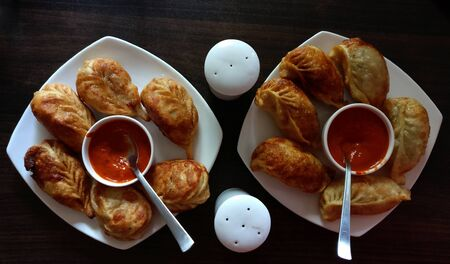 Veg fried cheese momos with sauce in white plates on a wooden table 写真素材
