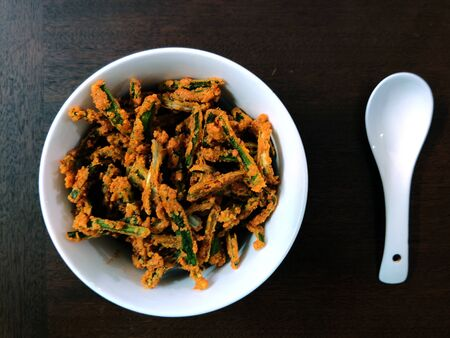 Kurkuri Bhindi or Crispy Lady Finger or Okra Fry served in a bowl on a wooden table with a white spoon Imagens