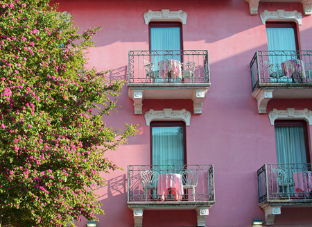 Tree in bloom and beautiful pink house with balconies in Sirmione, Italy Imagens