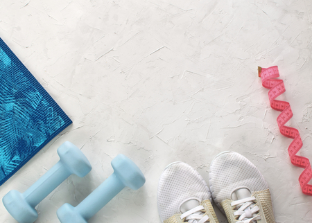 Fitness equipment on white concrete background with place for text
