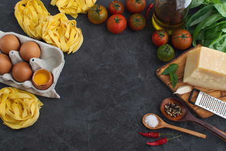 Italian pasta and sauce ingredient background top view on dark concrete background Banco de Imagens