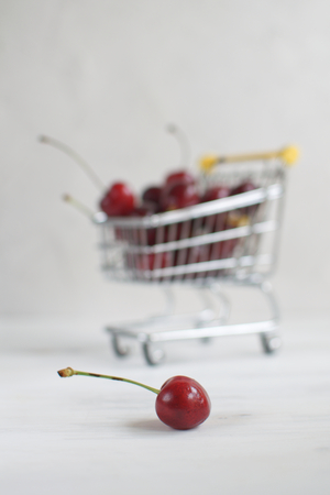Summer shopping or healthy eating concept, selective focus on fresh cherry with small shopping cart full of fresh cherries on the background, copy space Banco de Imagens