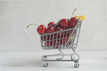 Summer shopping or healthy eating concept, fresh cherries in a small shopping cart on white background, copy space