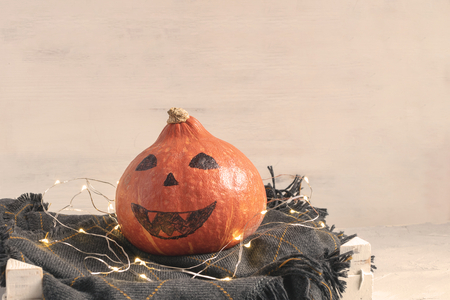 Halloween decoration concept - Pumpkin with drawn face on checkered knitted plaid, garland lights. Copy space, white background. Toned.