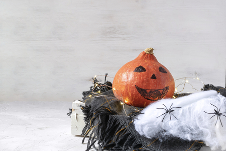 Halloween decoration concept - Pumpkin with drawn face on checkered knitted plaid, garland lights, spiders on web. Copy space, white background