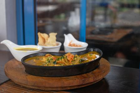 Close up of shrimps curry in a pan, rice, lentil dhal and Pol Sambol - sri lankan cuisine, menu design