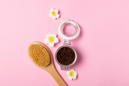 Skincare concept, weight loss - natural organic anticellulite coffee scrub in glass jar, wooden massage brush, pink background, flat lay, copy space