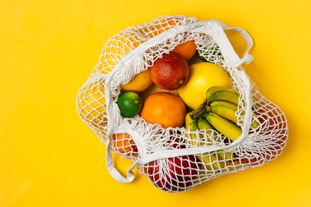 Organic fruits variety in cotton mesh reusable shopping bag, banana, mango, orange, lime, grapefruit, yellow background, top view, copy space - recycling, sustainable lifestyle, zero waste, no plastic