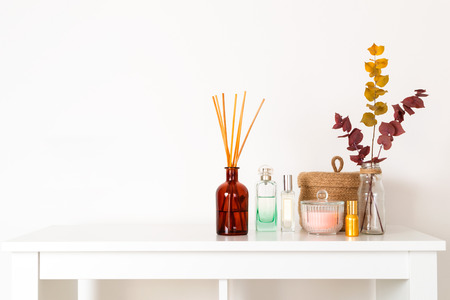 Minimal composition, scandinavian nordic hygge style, home interior - scent aroma diffuser with wooden sticks, perfume, small straw basket, dried eucalyptus branches, white shelf