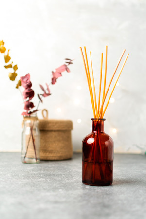 Minimal composition, scandinavian nordic hygge style, home interior - scent aroma diffuser with wooden sticks, small straw basket, dried eucalyptus branches, gray, vertical, selective focus