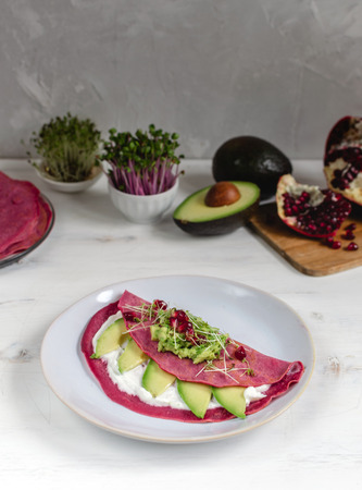 Tasty appetizing beetroot pancakes served on plate with avocado, cress sprouts and pink radish, white wooden table - vegan or vegetarian food concept.