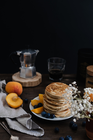 Beautiful served rustic breakfast - selective focus of stack of american pancakes with blueberries, peach, Gypsophila flowers, moka coffee machine, wooden table