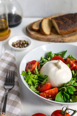 Fresh salad with italian burrata cheese, juicy tomatoes, balsamic vinegar and olive oil - healthy eating