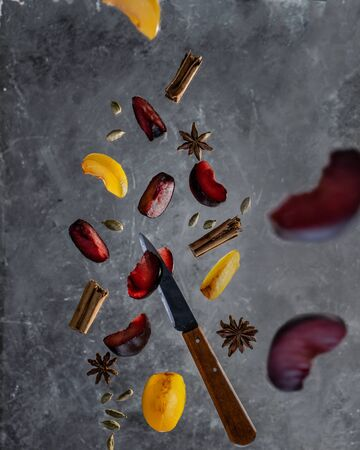 Plums with cinnamon, cardamom and anise spices on dark background in flying motion