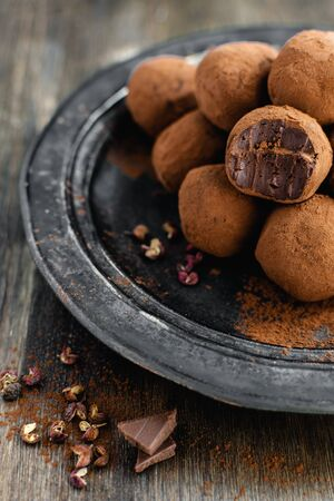 Delicious dark chocolate candy truffles with sichuan pepper on dark background