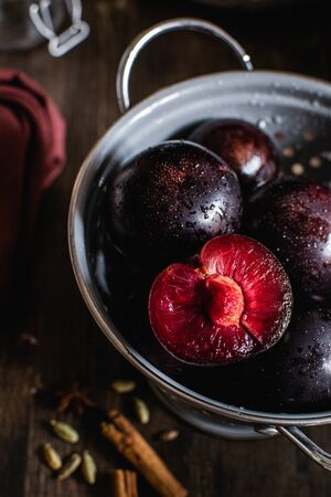 purple plums in gray colander on dark wooden background with cardamom, cinnamon and star anise spices, fall harvesting season