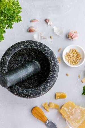 Process of preparation traditional italian pesto genovese sauce with mortar and pestle, top view