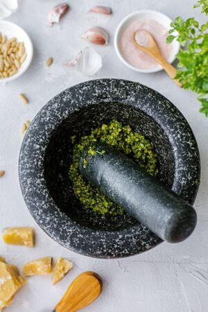 Herstellungsprozess traditionelle italienische Pesto Genovese-Sauce mit Mörser und Stößel, Ansicht von oben Standard-Bild