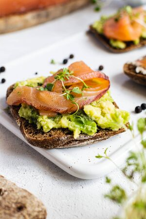 Healthy omega 3 breakfast or brunch - rye bread, smoked salmon, avocado, cucumber and microgreens Stock Photo