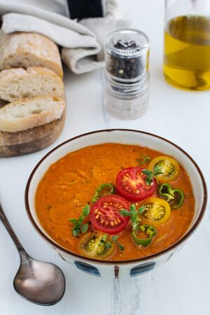 Traditional spanish tomato soup gazpacho in a bowl, on white wooden background Stock Photo