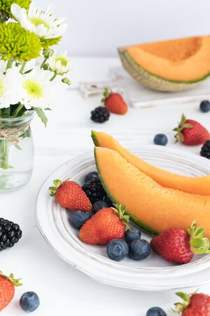 Fruit and berries variety on white wooden table