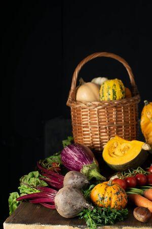 Dark still life, wicker basket with organic vegetables assortment