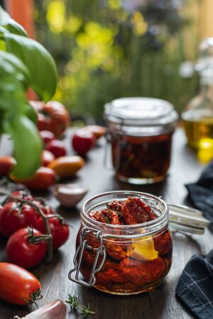 Italian cuisine, dried tomatoes in glass jar with aromatic herbs, thyme, basic, garlic, olive oil on rustic wooden table