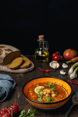 Vegetables, lentils and chickpeas vegetarian or vegan soup, source of protein, on brown wooden table
