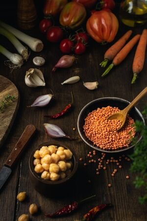 Vegetable assortment, lentils, chickpeas on brown wooden table, top view, vegetarian vegan groceries