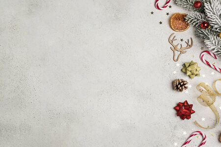 Christmas composition flat lay, fir tree, gingerbread, cookie cutter, candy cane, dried orange, ornaments, pinecone on light gray background, copy space