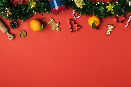 Christmas composition flat lay, tinsel, gingerbread, cookie cutter, candy cane, tangerine, ornaments, rolling pin, pinecone on red background, copy space