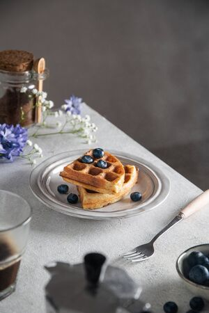 Fresh baked breakfast belgian waffles with honey and blueberries, on gray table 스톡 콘텐츠 - 140992577