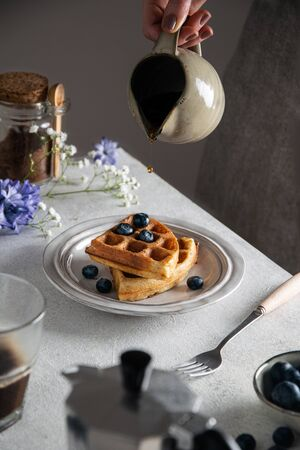 Fresh baked breakfast belgian waffles with honey and blueberries, on gray table