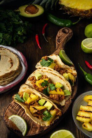 Traditional mexican pork tacos al pastor, corn tortilla, avocado, lime, chili pepper, pineapple, cilantro on rustic wooden table