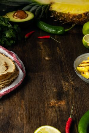 Food frame ingredients for mexican tacos, corn tortillas, chili pepper, pineapple, avocado, cilantro, dark wooden table, copy space 스톡 콘텐츠