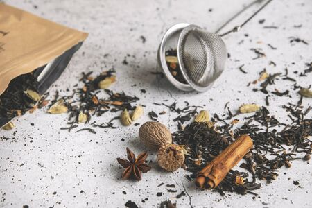 Masala chai black spiced tea with spices, cinnamon, nutmeg, cardamom, star anise, clove on white table